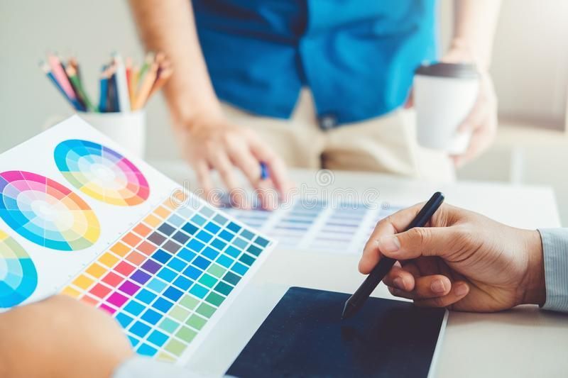 Two Graphic designer drawing on graphics tablet and color palette guide at workplace.  stock image