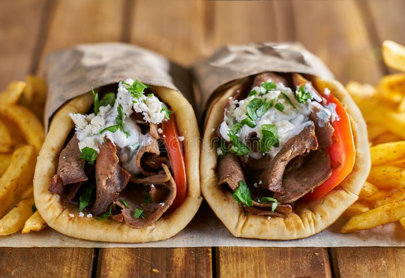 Two greek gyros with seasoned fries on wax paper stock photo