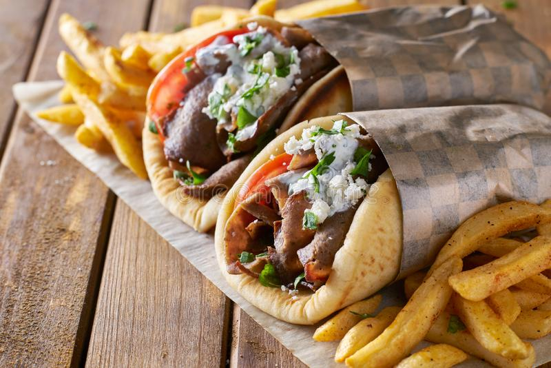 Two greek gyros with shaved lamb and french fries stock photos