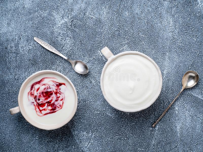 Two greek yogurt in white bowl on grey blue concrete stone table. Top view stock images