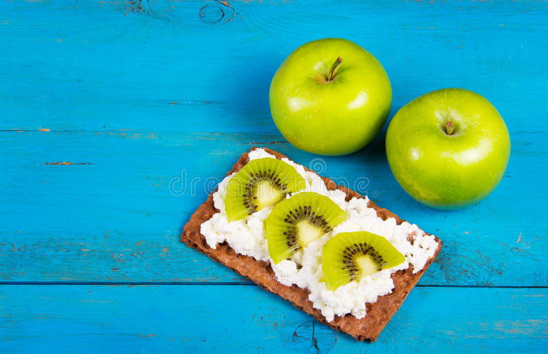 Two green apple and healthy grain sandwich with cream cheese and kiwi slices. A useful homemade breakfast. Vegetarian food. Healthy and tasty food. Copy space royalty free stock images