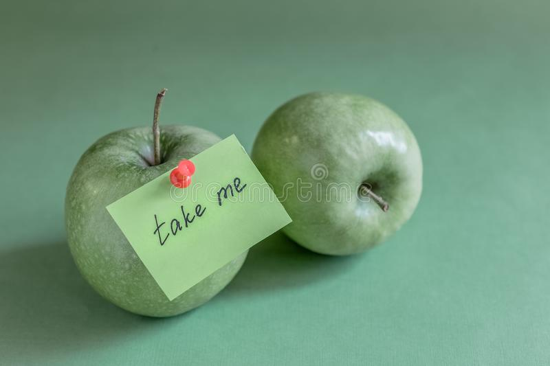 Two green apples note. Two green apples on green background, note on apple, red pin, take me stock photos