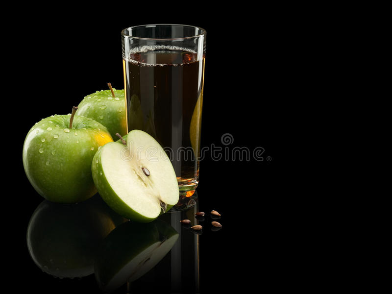 Two green apples and juice. Two green apples, seeds and juice glass are isolated on black royalty free stock photography