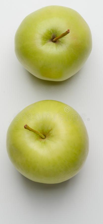 Two green apples on white. Background royalty free stock photo