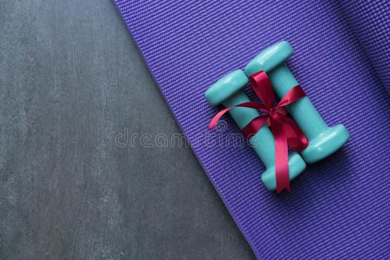 Two green dumbbell with red gift bow on a yoga mat background. Sport and healthy concept royalty free stock photography