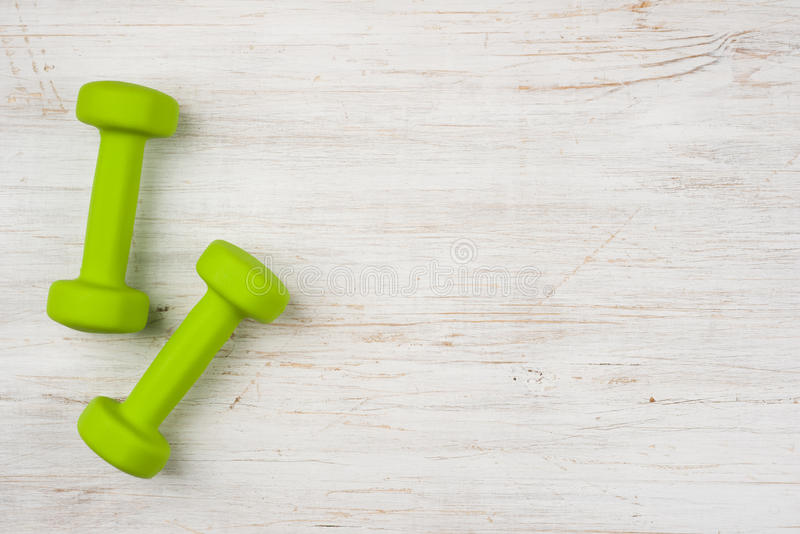 Two green dumbbells on wooden background with copy space stock photos