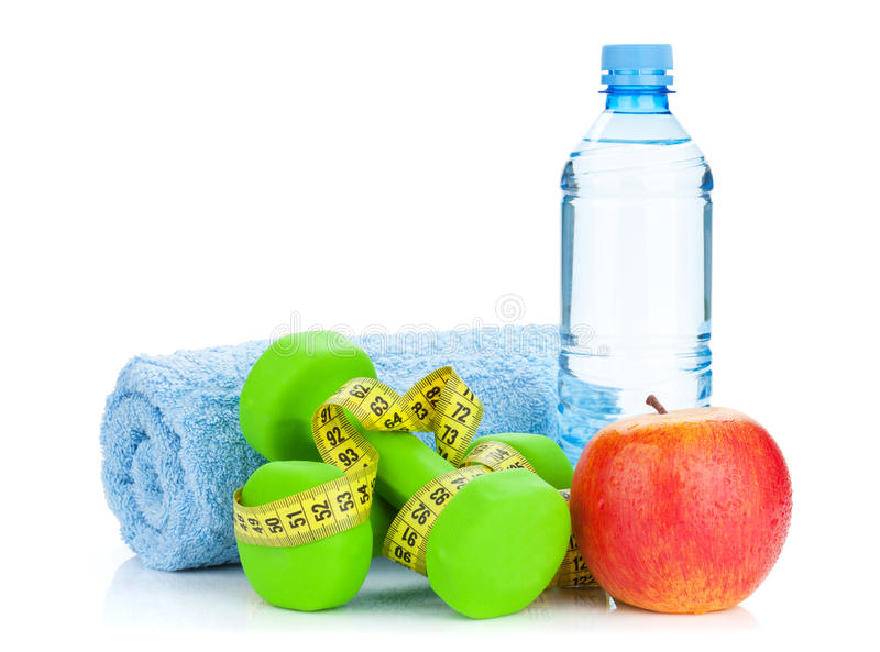 Two green dumbells, tape measure, apple and water bottle. Fitness and health. Isolated on white background royalty free stock photo