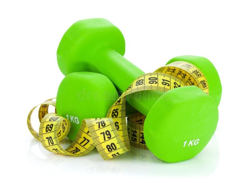 Two green dumbells and tape measure. Fitness and health. On white background royalty free stock photo