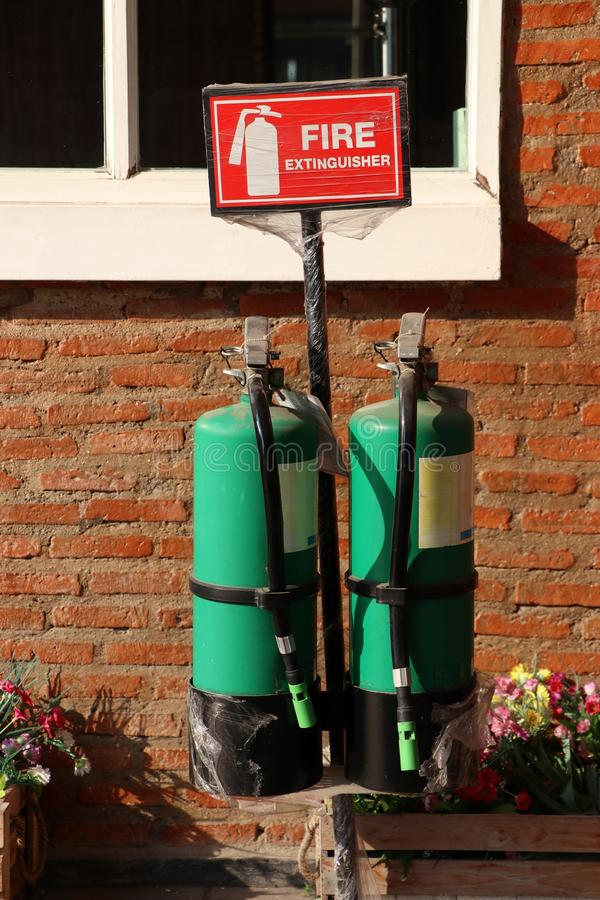 Two green fire extinguisher with the red sign and white text and symbolic icon on brick wall. And window background stock photos