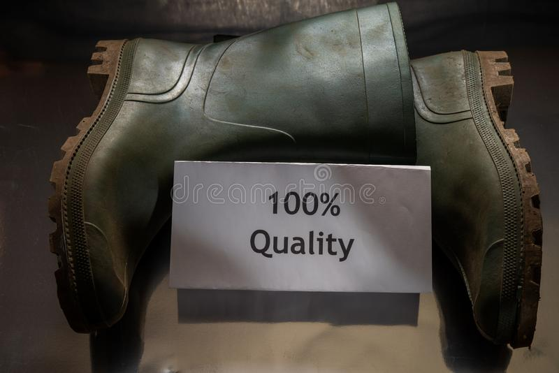 Two green rubber boots with note `100% Quality` are on the dark background/table. World Quality Day. royalty free stock image