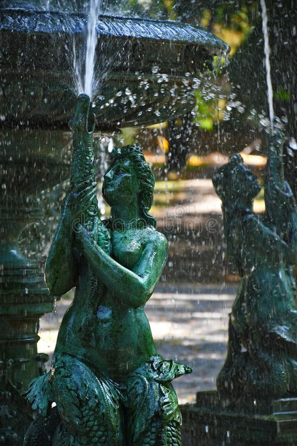 Two green sirens in fountain in the park of Vrsac city in Serbia. Photo represents two sirens in fountain in the park of Vrsac city in SerbiannPhoto is edited in royalty free stock photo