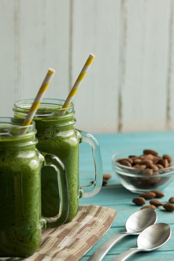 Two green smoothies in mason jar mugs with straws on a table wit royalty free stock images