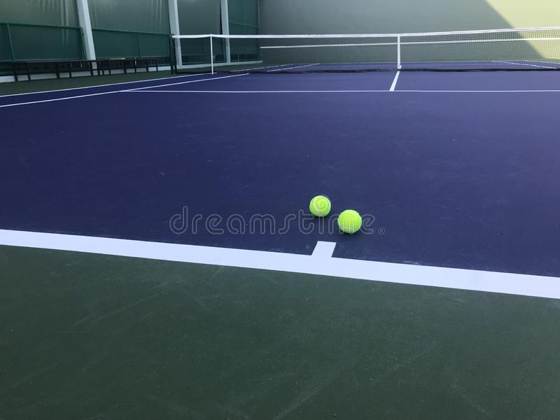 Two green tennis balls put on blue tennis court with net on background royalty free stock image