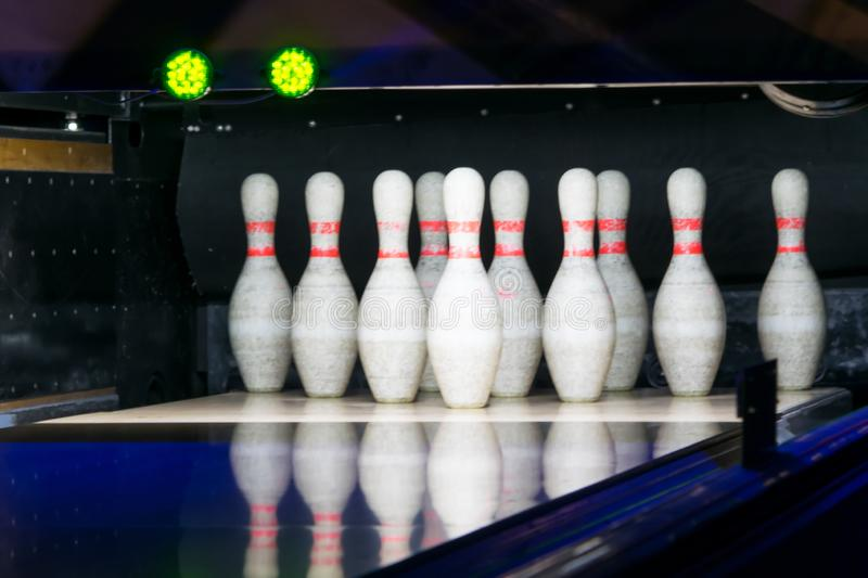Two green traffic lights in a bowling club over a row of white pins, dark background royalty free stock image