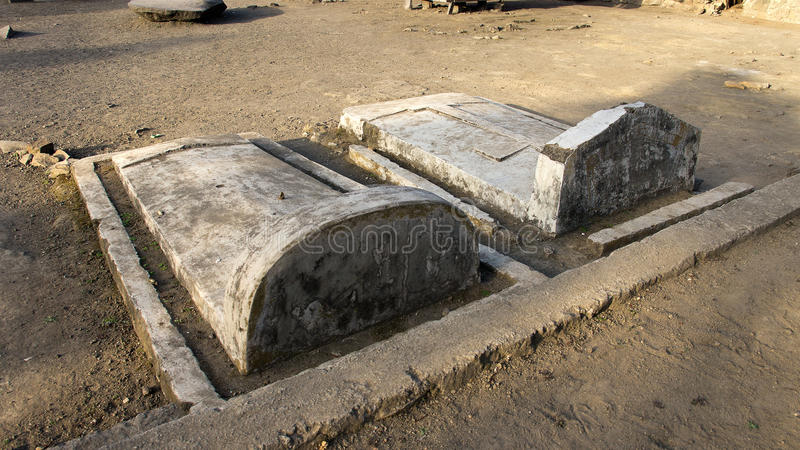 Two grey colored stone graves with tombstones at Bena a traditional village of the Ngada people in Flores. royalty free stock photos