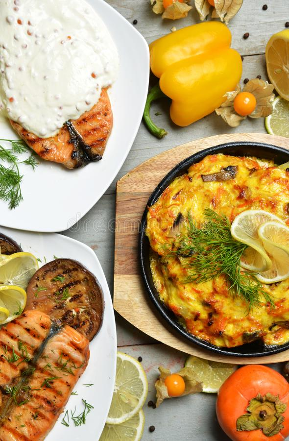 Two grilled salmon fish steaks with white cheese sauce and vegetables royalty free stock image