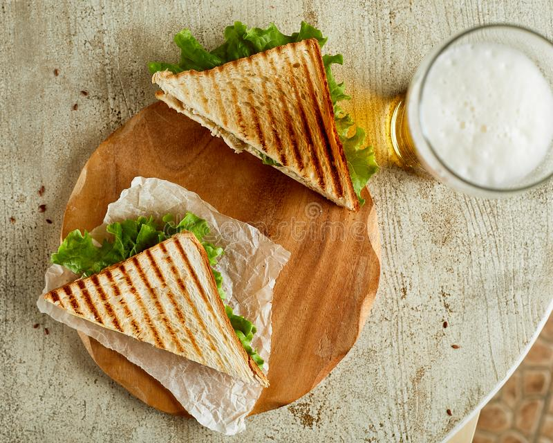 Two grilled sandwiches, served on backing paper with glass of be. High angle view of two grilled sandwiches, served on backing paper with glass of beer royalty free stock image