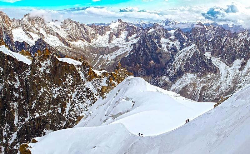 Two groups of alpinists mountaineers walking ascending snow glacier slope in Mont Blanc, Chamonix, France, Alps royalty free stock photo