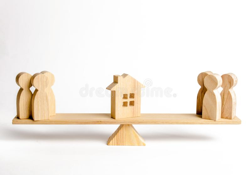 Two groups of people on the scales are suing the house. Conflict of interests and claims regarding the ownership of house. Illegal. Seizure of property, the stock photos