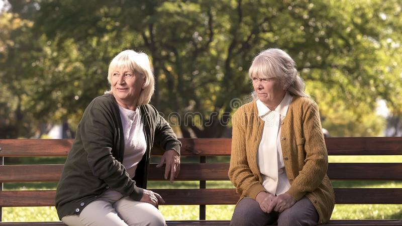 Two grumpy old ladies judging passerby people, sitting on bench in park, pension royalty free stock photography