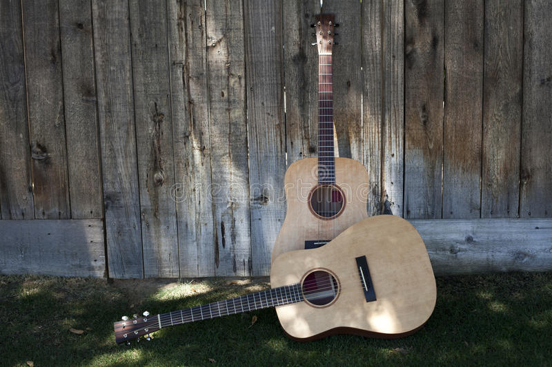 Two Guitars Against a Fence royalty free stock photography
