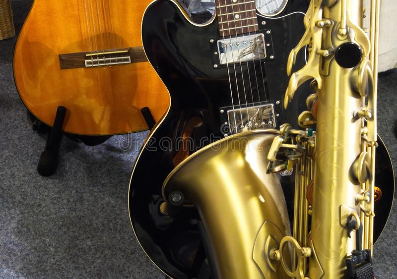 Two guitars and a saxophone. Detail of trhree instruments an acoustic guitarr, an electric guitar and a saxophone stock images