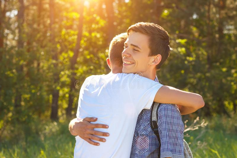 Two guys friends hugging when meeting the concept of happiness stock photo