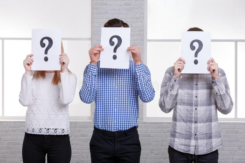 Two guys and a girl stand side by side close their faces with sheets with question marks close-up royalty free stock images