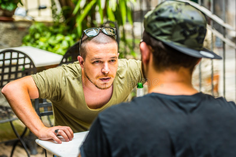 Two guys having an argument. Two young guys having a beer in an outdoor bar and and having an intense argument. Threatening each other with violent hand gestures stock images