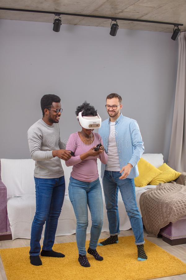 Two guys help african woman trying on virtual reality glasses for the first time stock photos