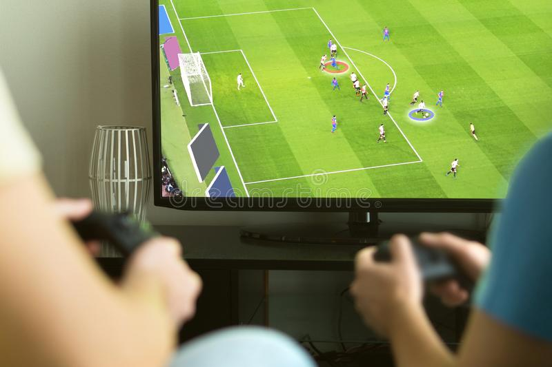 Two guys playing imaginary multiplayer soccer or football game stock images