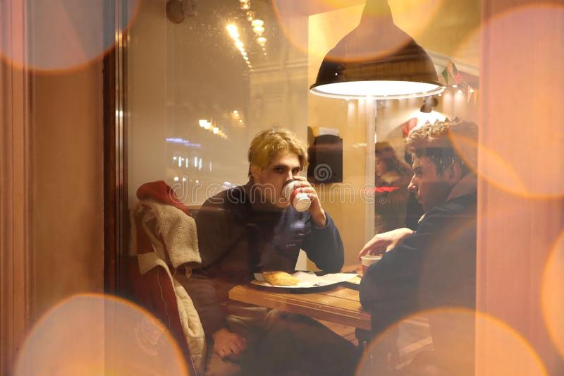 Two guys are sitting in a cafe and drinking coffee in a friendly way talking and looking at what is happening outside the window. Night winter Petersburg stock image