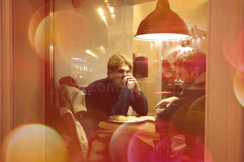 Two guys are sitting in a cafe and drinking coffee in a friendly way talking and looking at what is happening outside the window. Night winter Petersburg stock photo