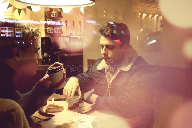 Two guys are sitting in a cafe and drinking coffee in a friendly way talking and looking at what is happening outside the window. Night winter Petersburg royalty free stock photo