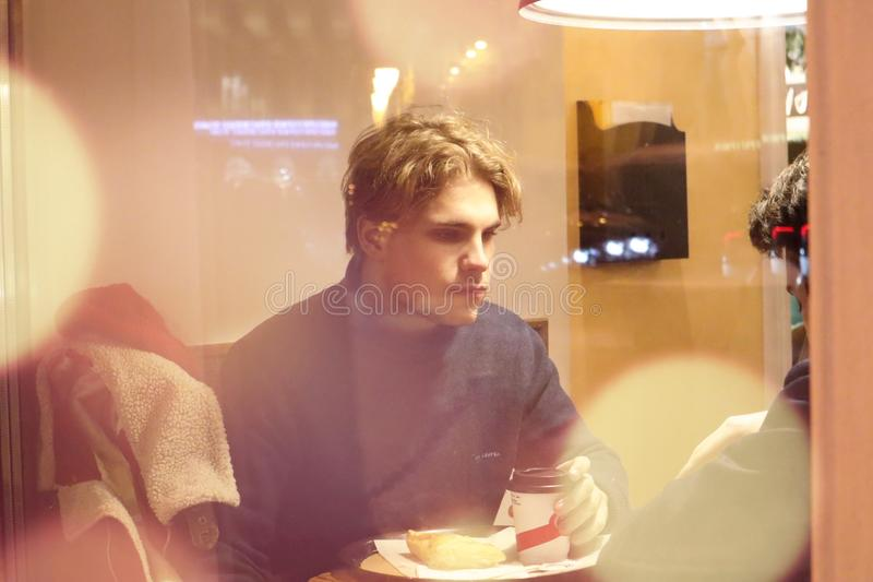 Two guys are sitting in a cafe and drinking coffee in a friendly way talking and looking at what is happening outside the window. Night winter Petersburg stock photography