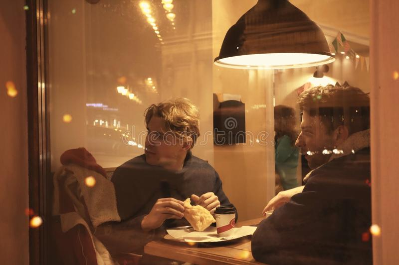 Two guys are sitting in a cafe and drinking coffee in a friendly way talking and looking at what is happening outside the window. Night winter Petersburg stock images