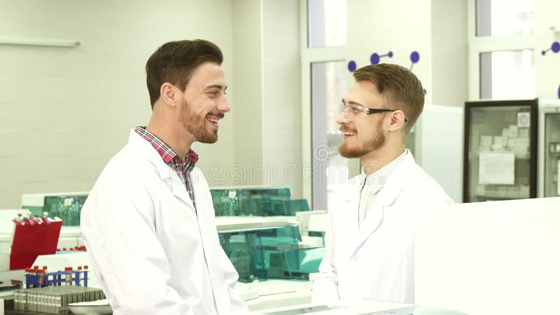 Two colleagues of laboratory assistants communicate during a break at work stock photos