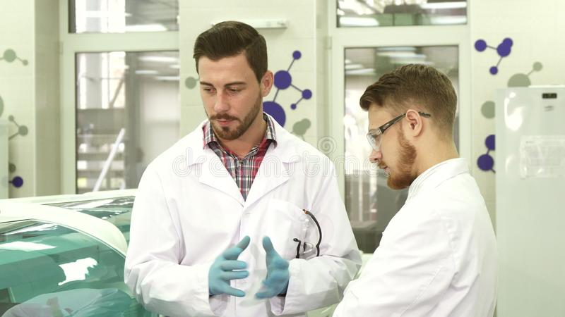 Two young laboratory assistants discuss the nuances of their workflow. Two guys are standing in the lab. They are watching the work process. Laboratory stock photos