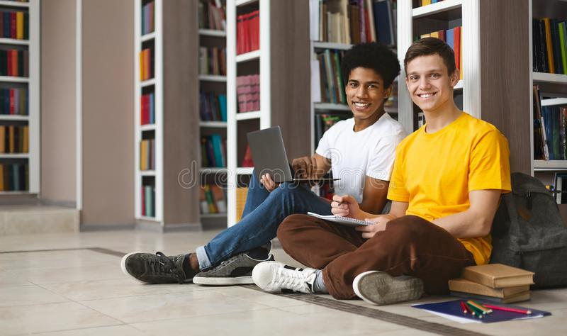 Two guys studying on floor in library, smiling at camera. Two young multi ethnic students studying on floor at bookshelf in library and smiling at camera, copy royalty free stock images