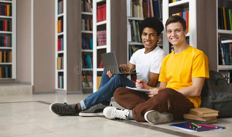 Two guys studying on floor in library, smiling at camera stock photography