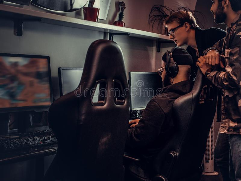 Two guys watch their friend play video games in a gaming club or internet cafe. Two guys watch their friend play video games in a gaming club stock photography
