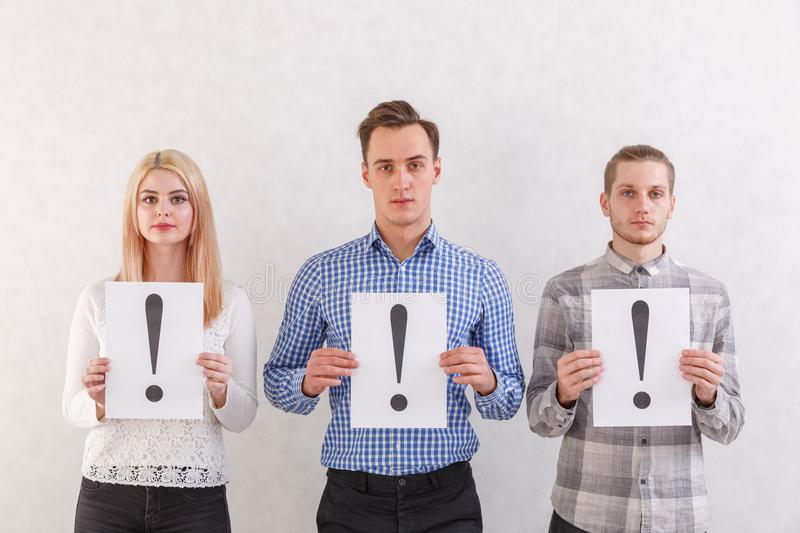 Two guys and a girl stand next to keep the sheets with exclamation marks on a gray background royalty free stock photography