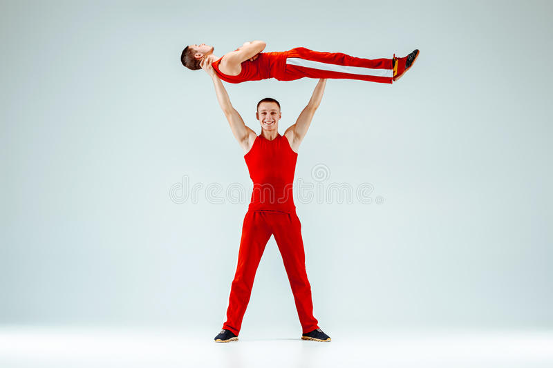 The two gymnastic acrobatic caucasian men on balance pose. The two gymnastic acrobatic caucasian men posing in balance posture on gray studio background stock images