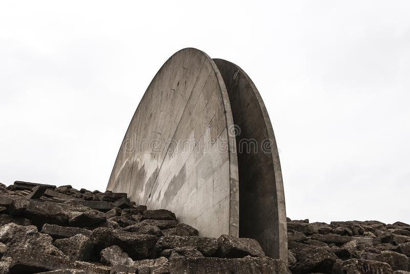 Two half concrete sculptures. Placed in a rock wall with concrete blocks on both sides of the sculptures stock photo