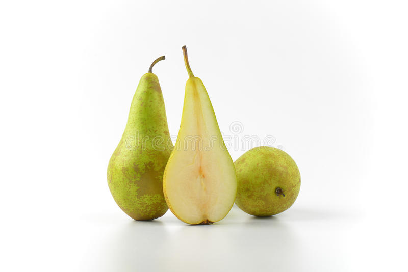 Two and a half pears. Two whole fresh green pears and one half royalty free stock photo
