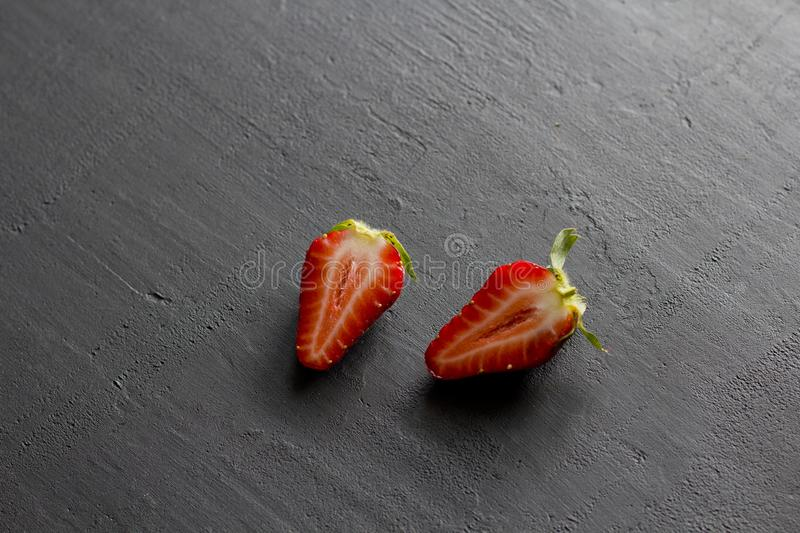 Two half strawberries, cut red beautiful strawberries close-up, on a black dark concrete background. Top View, Copy Space For Your. Text stock images
