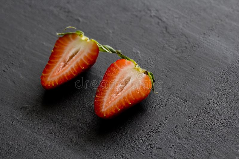 Two half strawberries, cut red beautiful strawberries close-up, on a black dark concrete background. Top View, Copy Space For Your. Text. Fruit erotica stock images