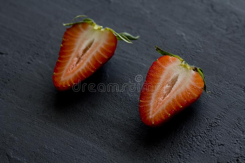 Two half strawberries, cut red beautiful strawberries close-up, on a black dark concrete background. Top View, Copy Space For Your. Text. Fruit erotica royalty free stock images