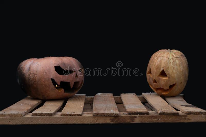 Two Halloween pumpkins on the boards against each other on a black background. Two spooky Halloween pumpkins on the boards against each other on a black stock photography