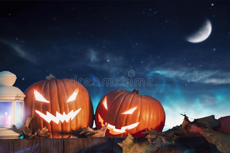 Two halloween pumpkins on fence with starry sky stock images